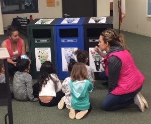 teacher with kids in front of recycling bins